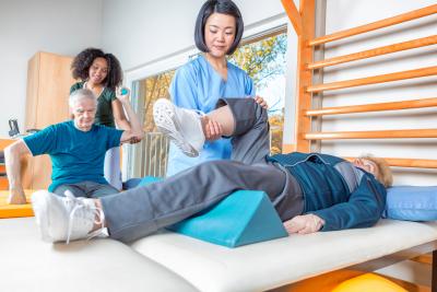 Multi racial nurses helping elder patients.